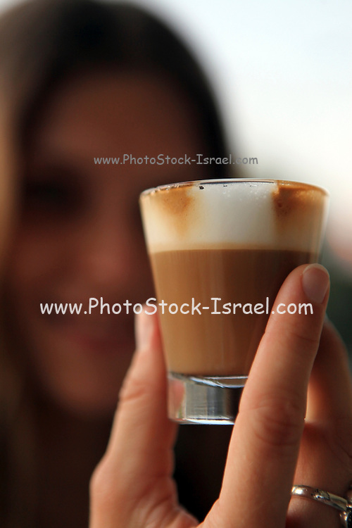 Small glass of Espresso Coffee out of focus woman in the background