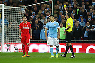 Alberto Moreno of Liverpool (l) receives a yellow card from referee Michael Oliver.  Capital One Cup Final, Liverpool v Manchester City at Wembley stadium in London, England on Sunday 28th Feb 2016. pic by Chris Stading, Andrew Orchard sports photography.