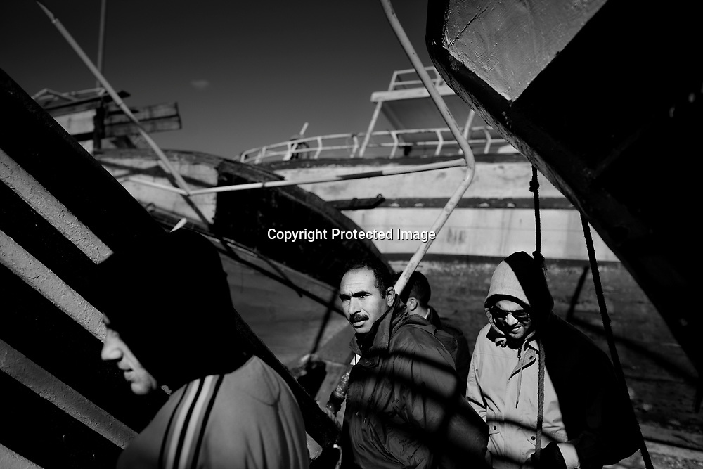 Migrants walking through old tunisian fishingboats that the authorities have put on land