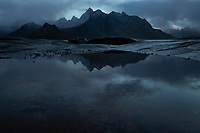 Rugged mountain peaks of Flakstadøy reflect in tidal pond, Lofoten Islands, Norway