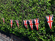 Patriotic bunting on display on a hedge outside a garden on 7 May 2020 in Saltburn-by-the-Sea, Cleveland, United Kingdom. VE Day - or Victory in Europe Day - marks the day towards the end of World War Two WW2 when fighting against Nazi Germany in Europe came to an end. On 8 May 1945, Prime Minister Winston Churchill made an announcement on the radio at 3pm that the war in Europe had come to an end, following Germanys surrender the day before.