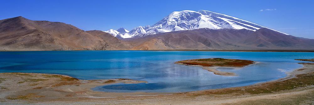 Kalakuli Lake reflects snow-covered Mustagata Peak, in the Pamir Mountains, Xinjiang, China.