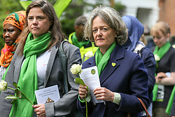 © Licensed to London News Pictures. 14/06/2019. London, UK. Kensington and Chelsea council leader, Elizabeth Campbell (R) wears a symbolic green scarf as she takes part in a silent procession marching from St Helen's Church to Grenfell Tower to commemorate the second anniversary of the Grenfell Tower fire. On 14 June 2017, just before 1:00 am a fire broke out in the kitchen of the fourth floor flat at the 24-storey residential tower block in North Kensington, West London, which took the lives of 72 people. More than 70 others were injured and 223 people escaped. Photo credit: Dinendra Haria/LNP