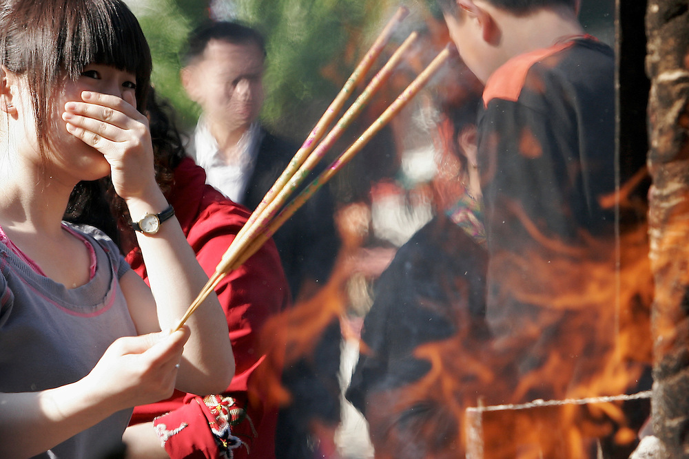 A woman adds incense to a fire raging inside the large front burner at Baiyuguan.  Baiyuguan,called White Cloud Temple in English, is over 1,200 years old and stands the south west of Beijing, China.  White Cloud Temple is the largest Daoist structure in Beijing and home of the Dragon Gate sect of Daoism.