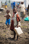 A boy carries jericans of water in the Mugunga II IDP camp on the outskirts of Goma, Democratic Republic of Congo, on Wednesday December 17, 2008.