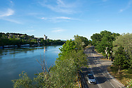 A Peugeot car drives beside the Rhone River in Avignon, France. Across the river is the medieval tower called Tour Philippe le Bel, located in Villeneuve-lès-Avignon.