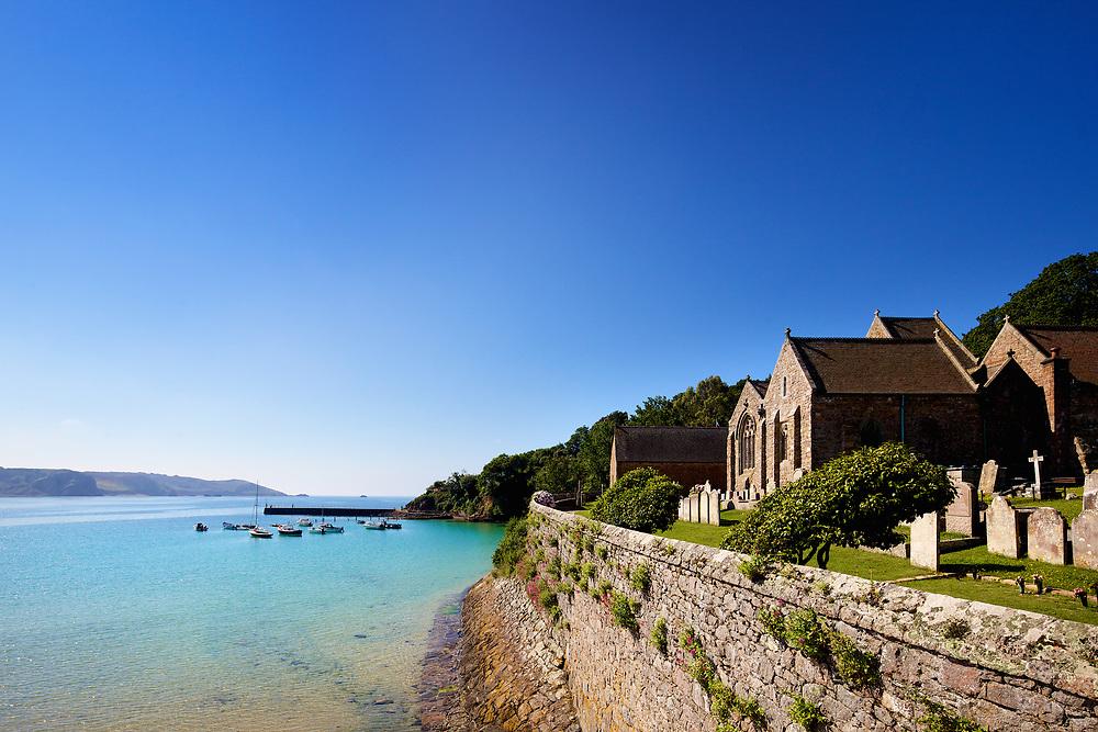 St Brelade's Church overlooking St Brelade's beach at high tide in Jersey, Channel Islands