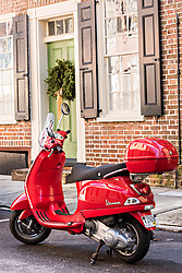 December 21, 2017 - Charleston, South Carolina, United States of America - A red Vespa scooter parked in front of a historic home decorated with a Christmas wreath on Tradd Street in Charleston, SC. (Credit Image: © Richard Ellis via ZUMA Wire)