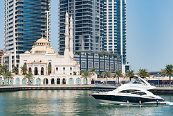Contrast between motor boat and new mosque at Dubai Marina district in UAE