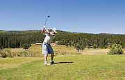 Golfer swings at Valle Escondido Taos Canyon Golf Course