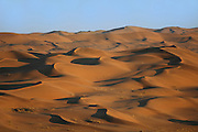 Nahe der Gobabeb Forschungsstation kann man die Dünen der Namib erklimmen und hat bei Sonnenaufgang einen atemberaubenden Ausblick über das rote Sand-Meer, das durch die Kraft des Windes geformt wird. Die Dünen wandern dabei in nord-westliche Richtung vorwärts, bis sie auf das Bett des Kuiseb-Flusses treffen. Das Wasser in diesem Rivier (Trockenfluss) fließt selten, aber dennoch häufig genug, um ein Fortschreiten der Dünen zu verhindern.  Position 23°33.704 S, 15°02.466 E l Namib desert. Close to the Gobabeb training and research centre, at 23°33.704 S, 15°02.466 E   The Namib Dune Sea is formed by the powerful force of desert winds. These winds gradually push the dunes in a north-westerly direction.