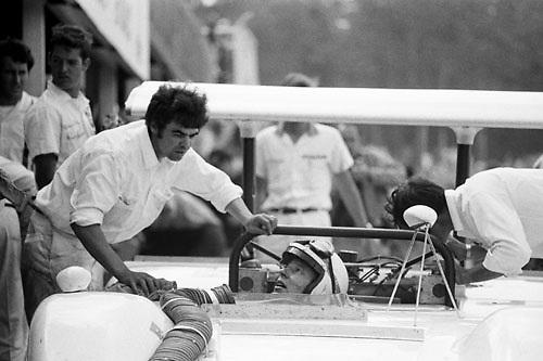 John Surtees, Chaparral McLaren M12, confers with engine man Barry Crowe in pit lane at 1969 Watkins Glen Can-Am; Photo by Pete Lyons 1969/ © 2014 Pete Lyons / petelyons.com;