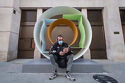 "© Licensed to London News Pictures. 01/10/2020. LONDON, UK. A man sits in front of ""Lift Going Up, Lift Going Down"", 2019, by David Annesley, displayed on Cork Street as part of the inaugural Mayfair Sculpture Trail which will be on show to the public for the month of October.  The sculpture trail forms part of the seventh, annual edition of Mayfair Art Weekend which celebrates the rich cultural heritage of Mayfair as one of the most internationally known, thriving art hubs in the world with free exhibitions, tours, talks and site-specific installations available to the public.  Photo credit: Stephen Chung/LNP"