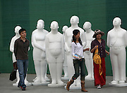 People walk amongst sculptures on display at a gallery in Beijing's trendy Dashanzi Art District May 4, 2007.