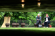© Licensed to London News Pictures. 31/05/2012. London, UK A couple sitting outside the pavilion. The press preview today 31st May 2012, of The Serpentine Gallery Pavilion 2012, designed by Herzog & De Meuron and Ai Weiwei. The pavilion is the twelfth commission in the gallery's series of annual pavilions.. Photo credit : Stephen Simpson/LNP