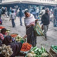 A woman sells vegetables in an outdoor market in Kathmandu, Nepal, 1986.
