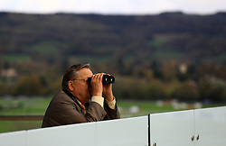 A spectator looks through binoculars during day two of the Showcase at Cheltenham Racecourse
