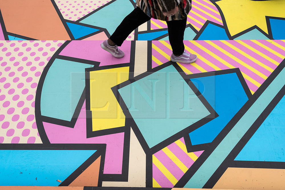 """© Licensed to London News Pictures. 07/04/2018. LONDON, UK.  A visitor walks across the colourful entrance mural by graphic designer artist Supermundane outside """"Sense of Space"""", an art pop-up which opened to the public in Broadgate.  Comprising four rooms to challenge the visitor's sensory perceptions through art, the installation is open until 18 May.  Photo credit: Stephen Chung/LNP"""