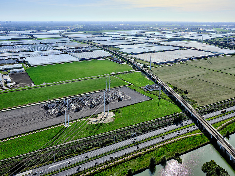 Nederland, Zuid-Holland, Zoetermeer, 14-09-2019; hogesnelheidslijn HSL kruist autosnelweg A12, ten Oosten van Zoetermeer.  In de achtergrond het kassengebied van Bleiswijk, aan de horizon de skyline van Rotterdam. Naast de hogesnelheidslijn hoogspanning-verdeelstation van Tennet.<br /> High-speed line HSL crosses the A12 motorway, east of Zoetermeer<br /> <br /> luchtfoto (toeslag op standard tarieven);<br /> aerial photo (additional fee required);<br /> copyright foto/photo Siebe Swart