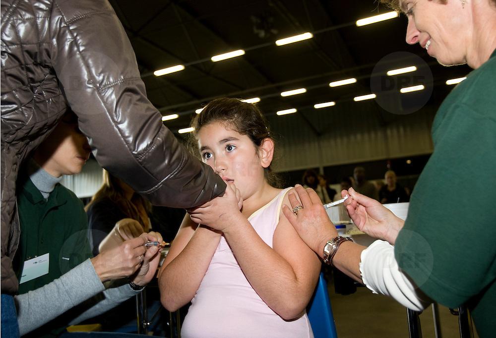 """Nederland Rotterdam 8 oktober 2008 Foto: David Rozing ..Meisje krijgt tegelijkertijd 2 vaccinaties in bovenarmen op Vaccinatiedag AHOY ..Vaccinatiedag AHOY in teken van overgewicht en opvoeden.Vandaag werden in AHOY Rotterdam zo'n 4.000 kinderen uit het Noorden van Rotterdam gevaccineerd tegen de infectieziekten difterie, tetanus en polio (DTP) en bof, mazelen en rode Hond (BMR). Na de vaccinaties kunnen ouders gebruik maken van advies van een diëtist en van een pedagoog..Twee keer per jaar houdt de GGD Rotterdam-Rijnmond een grote vaccinatiedag voor 9-jarigen. Op 8 oktober krijgen ongeveer 4000 kinderen een vaccinatie tegen ernstige infectieziekten als difterie, tetanus en polio (DTP) en/of bof, mazelen en rode Hond (BMR). Enkele 9-jarigen krijgen ook nog een Hibvaccinatie (tegen Haemophilus influenzae type b). Er worden ook zo'n 500 kinderen gevaccineerd die zich pas in Rotterdam hebben gevestigd. Voor deze kinderen moet soms het buitenlandse schema worden ingepast in het Nederlandse Rijksvaccinatieprogramma (RVP).""""??Meten, wegen en opvoedingsadvies??De GGD grijpt de vaccinatiedag aan om méér te doen dan de bescherming tegen infectieziekten. De kinderen kunnen na de twee prikken meteen doorlopen voor het bepalen van hun lengte en gewicht. Er zijn diëtisten aanwezig, zodat ouders en kinderen zich kunnen laten adviseren over gezonde voeding en beweging. En als ouders vragen hebben over de opvoeding van hun kind kunnen zij deze ter plekke stellen aan één van de veertien aanwezige pedagogen. ??Activiteiten voor kinderen over ontbijten??Er zijn allerlei activiteiten te doen in het teken van ontbijten. Een diëtist maakt samen met kinderen gezonde ontbijtjes. Er is een muzikale theatervoorstelling over het belang van ontbijten. Op een groot scherm wordt een filmpje vertoond en met een ontbijtquiz zijn drie fietsen te winnen. Alle kinderen krijgen een attentie mee naar huis.??Actieprogramma Voeding en beweging??De GGD houdt deze voedings- en bewegingsactiviteiten in het k"""