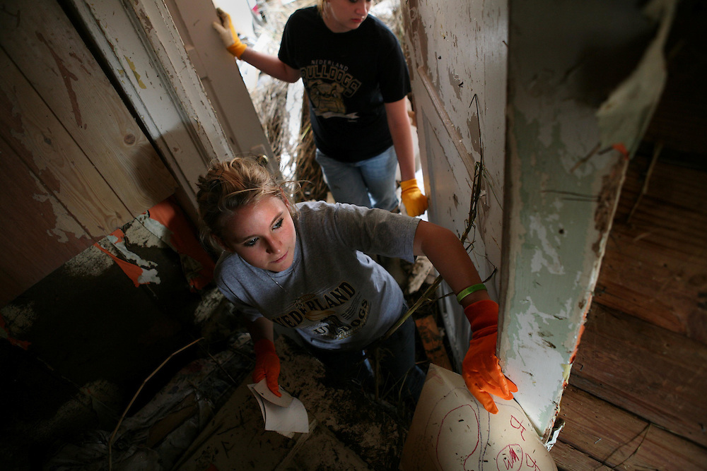 Marissa Berg, 12, front, leans into a debris-filled hallway as she shows her mother old photos and drawings  recovered from a bedroom closet in their home that was destroyed by Hurricane Ike in Sabine Pass Friday September 19, 2008.  In the background is Marissa's friend Christian Broseh, 13, of Port Neches.