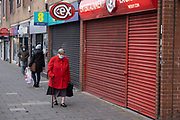 Shutters are down as many shops have had to close down during the second national lockdown continues with just over a week before the new tier system begins, and people, many of whom are wearing face masks, come to Kings Heath High Street, as all non-essential shops are closed while some remain trading on 23rd November 2020 in Birmingham, United Kingdom. The new national lockdown is a huge blow to the economy and for individual businesses who were already struggling with only offering limited services.
