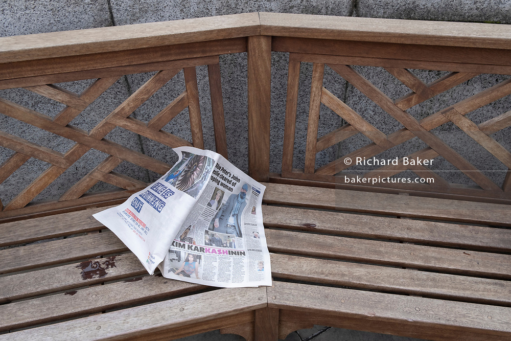 A copy of a newspaper with yesterday's news has been discarded on a bench outside the Bank of England in the City of London, the capital's financial district, on 20th October 2020, in London, England.