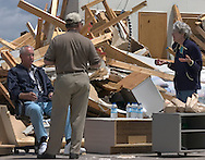 5/23/04 Hallam Neb, From left Curtis Schwaninger, Karl Hartman, and Joetta Schwaninger, rest while cleaning the mess from a tornado.  The Schwaninger's house was destroyed while they were at a graduation in Lincoln Neb.  Their house is about 1/2 mile east of Hallam, Neb.  Hartman is a family friend of the Schwaningers, and along with his wife, Phyllis came over to help clean up.  The Schwaningers have had the house about nine years.  (Photo by Chris Machian/Machian Photo)