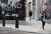 Signs for high end fashion and exclusive brands on New Bond Street, London, UK.