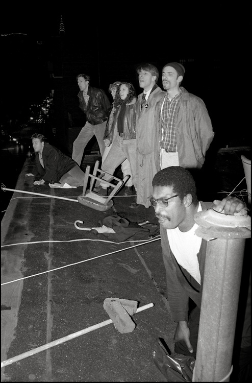 """In November of 1989, several ACT UP members unfurled a banner, from the rooftop of Outweek Magazine's offices, which was directly across the street from 69th Regimental Armory where the socialite, Pat Buckley, was co-chairing a black-tie benefit for the Design Industries Foundation for AIDS (DIFFA). Buckley was married to Syndicated columnist William F. Buckley who had written that people with AIDS should be tattooed as a means of """"personal protection"""" and characterized AIDS as a self-inflicted disease brought on by """"dope addicts"""" and """"sex-driven gays"""".<br /> <br /> Three members of ACT UP stood in front of the armory's entrance, dressed in tuxedos, and handed arriving guests fliers which quoted Mr. Buckley's remarks."""
