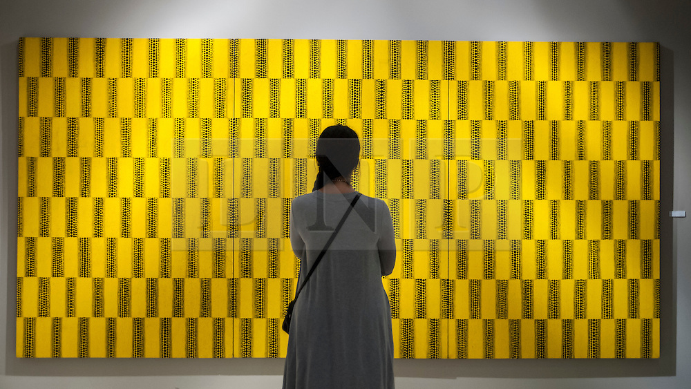 "© Licensed to London News Pictures. 24/06/2015. London, UK.   A visitor looks at Yayoi Kusama's ""Waves"", at the preview of Masterpiece London, the international cross-collecting Fair for art, antiques and design which takes place at The Royal Hospital Chelsea 25 June to 1 July. Photo credit : Stephen Chung/LNP"