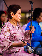 "29 APRIL 2017 - MINNEAPOLIS, MINNESOTA: A Thai woman plays a traditional Thai fiddle at Songkran Uptown in Minneapolis. Several thousand people attended Songkran Uptown on Hennepin Ave in Minneapolis for the city's first celebration of Songkran, the traditional Thai New Year. Events included a Thai parade, a performance of the Ramakien (the Thai version of the Indian Ramayana), a ""Ladyboy"" (drag queen) show, and Thai street food.     PHOTO BY JACK KURTZ"
