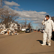 A man in a Hazardous Material suit drinks coffee provided by volunteers as he walks down a street littered with debris and wreckage left by Superstorm Sandy in Union Beach NJ. The storm-surge from Superstorm Sandy destroyed several oceanfront blocks of Union Beach, leveling homes or lifting them off their foundations, breaking them apart and moving them.