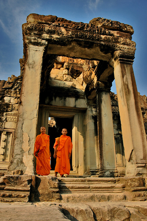 These two Cambodian Buddhist Monks were standing in one of the buildings (Library) located in the Angkor Wat temple complex, the world's largest single religious monument built for the king Suryavarman II in the early 12th century as his state temple and capital city.<br /> <br /> It is a massive three-tiered pyramid crowned by five lotus-like towers rising 65 meters from ground level is surrounded by a moat and an exterior wall. All the walls of the temple are covered inside and out with bas-reliefs and carvings. <br /> <br /> The ruins of Angkor, a UNESCO World Heritage Site with temples numbering over 1000, are hidden amongst forests and farmland to the north of the Tonle Sap Lake outside the modern city of Siem Reap, Cambodia. <br /> <br /> Angkor Wat has remained a significant religious centre since its foundation--first Hindu, dedicated to Vishnu, then Buddhist. Quite a few of the temples at Angkor have been restored and represent a significant site of Khmer architecture.
