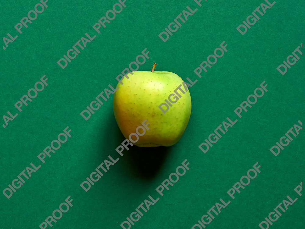 Above view of a Green apple isolated in a green background in studio