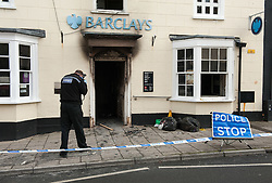 © Licensed to London News Pictures. 28/10/2015. Thornbury, South Gloucestershire, UK. Police and forensics attend a suspected raid on Barclays Bank in Thornbury High Street which occurred at 3.30am.  An ATM in a foyer corridor with 24 hrs access was targeted, and an explosion damaged the interior.  A gas bottle can be seen in the foyer corridor and a large hammer and crowbar were left at the scene. Photo credit : Simon Chapman/LNP