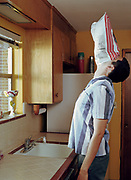Young man in kitchen, potato chip bag covering face, head back