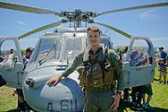 East Meadow, New York, USA. May 25, 2019. Second Class Petty Officer ERIK KOPECK, of Helicopter Sea Combat Squadron NINE HSC-9 based in Norfolk, Virgiania, poses with MH-60S helicopter at the U.S. Navy hosted aviation event, as part of Fleet Week, on Memorial Day Weekend at Eisenhower Park on Long Island. The helicopter is a search, research and rescue Naval carrier.