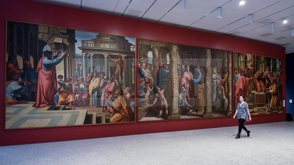 © Licensed to London News Pictures. 14/05/2018. LONDON, UK. A gallery staff member walks through the new Collection Gallery viewing copies of Raphael's paintings, 1483-1520, made by Sir James Thornill, at a photocall for the opening of the new Royal Academy of Arts (RA) in Piccadilly.  As part of the celebrations for its 250th anniversary year, redevelopment has seen the RA's two buildings, 6 Burlington Gardens and Burlington House, united into one extended campus and art space extending from Piccadilly to Mayfair.  Photo credit: Stephen Chung/LNP