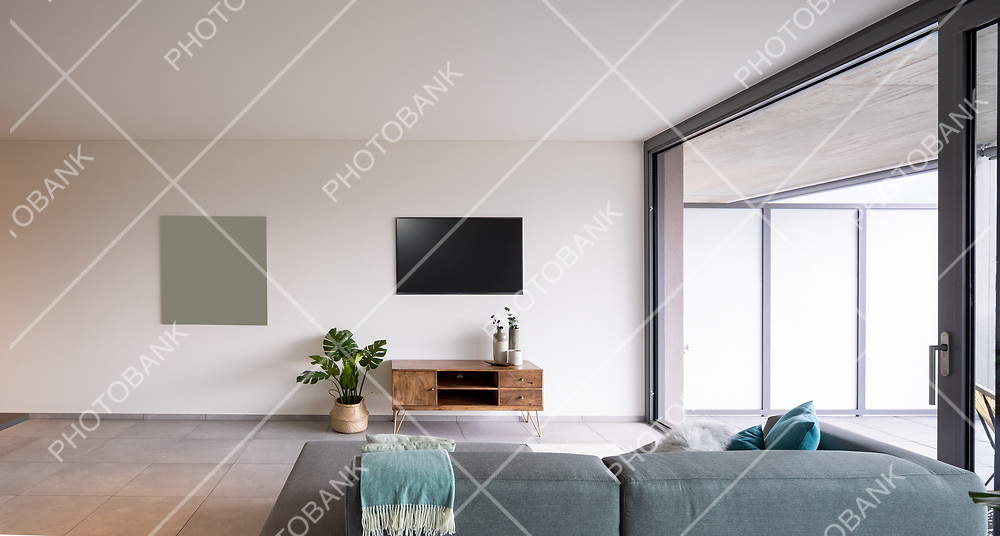interior of a living room with a sofa seen from behind. On the wall a television, minimalist furniture