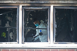 © Licensed to London News Pictures 07/03/2021. Greenwich, UK. Forensics can be seen at work through a window at the front of the property on the first floor. Police and London Fire Brigade forensic teams continue to work at the scene of a fatal fire that killed a five year old boy and has left the rest of his family in hospital. The property in Greenwich, South East London is still cordoned off today with flowers and balloons being placed at the scene. Photo credit:Grant Falvey/LNP