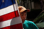 BIRMINGHAM, AL – OCTOBER 5, 2013: Brandon Vela, 15, holds the American flag during a rally organized by the Alabama Coalition for Immigrant Justice. The rally and march were intended to call attention to the need for immigration reform by Congress. CREDIT: Bob Miller for The New York Times