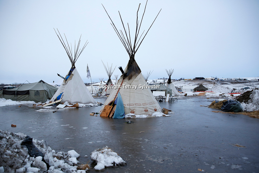 Tipis stand in frozen water at the main opposition camp against the Dakota Access oil pipeline on the edge of the Standing Rock Sioux Reservation on February 11, 2017, near Cannon Ball, North Dakota, United States.