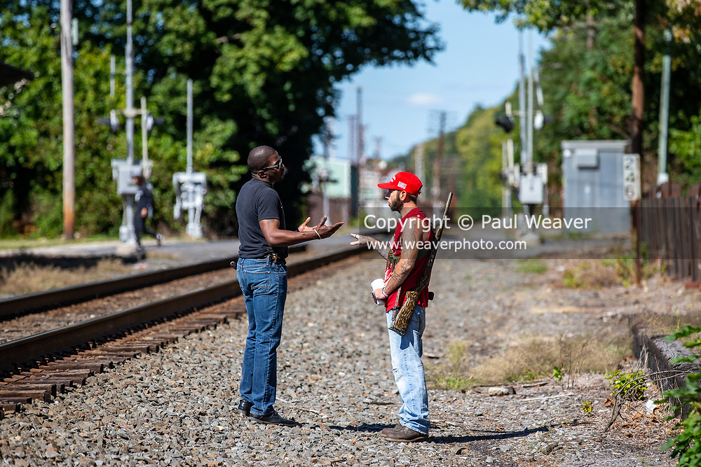 An armed counter-protester wearing a Make America Great Again hat and a Black Lives Matter protester speak as a BLM rally is going on in Milton, Pennsylvania on September 20, 2020.