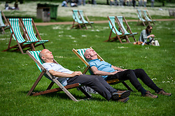 © Licensed to London News Pictures. 27/05/2021. LONDON, UK.  Men on deckchairs enjoying the sunshine and warmer temperatures in St James's Park after an unusually wet May so far.  The forecast for the Bank Holiday weekend is fine weather.  Photo credit: Stephen Chung/LNP