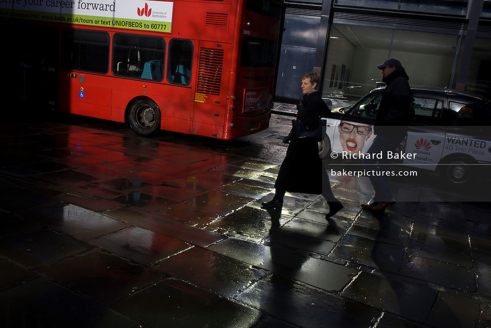 Pedestrians pass-by red London bus and taxi with female ad in strong sunshine after recent heavy rain showers.