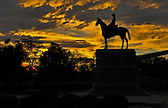 The Sun rises over Cavalry Parade Field and the statue of the Old Trooper at Fort Riley, Kansas.