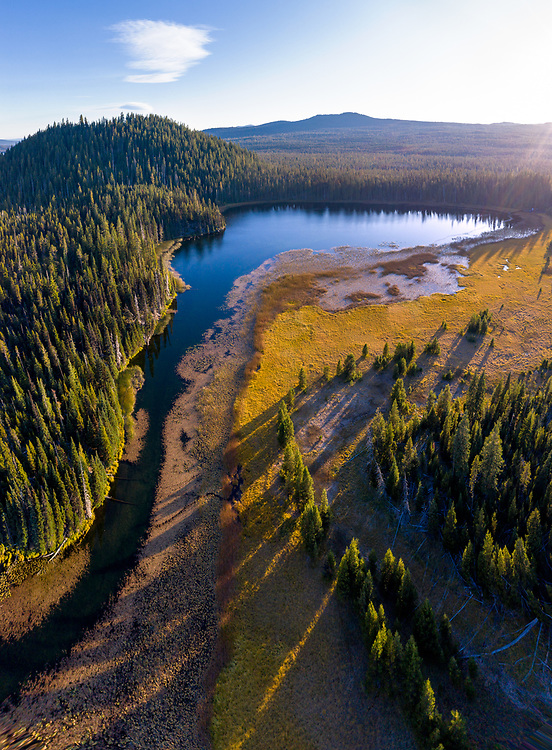 A late autumn afternoon drone flight over Hosmer Lake in the Oregon Cascades reveals the meandering channel of its water source.