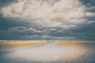 Scenic landscape of the wide beach sands at Holkham in north Norfolk, England with dog walkers
