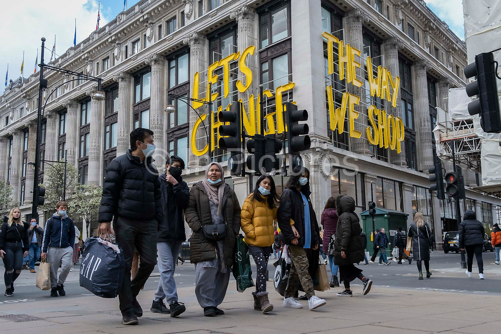 On the day that the UK government eased Covid restrictions to allow non-essential businesses such as shops, pubs, bars, gyms and hairdressers to re-open, the Selfridges department store displays the slogan about changing the way we shop, on 12th April 2021, in London, England.